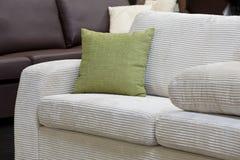 Piloow. Green pillow on the white velveteen sofa Stock Photos