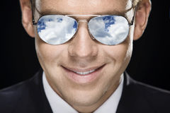 Pilot. Closeup portret of handsome pilot in glasses. Sky reflected in glasses Royalty Free Stock Photography