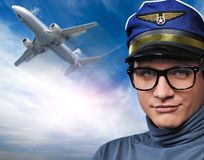 Pilot against flying plane. Handsome young pilot against flying plane Stock Image