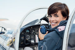 Pilot in the aircraft cockpit. Smiling female pilot in the light aircraft cockpit, she is holding aviator headset and looking at camera stock image