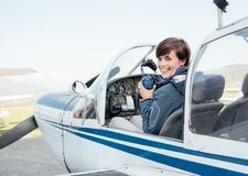Pilot in the aircraft cockpit. Smiling female pilot in the light aircraft cockpit, she is holding aviator headset and looking at camera royalty free stock photos