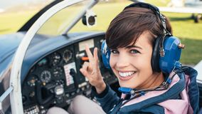 Pilot in the aircraft cockpit. Smiling female pilot in the light aircraft cockpit, she is wearing aviator headset and making a V sign Royalty Free Stock Photography