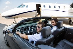 Pilot And Airhostess In Convertible Against Royalty Free Stock Photos