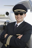 Pilot With Arms Folded Leaning On Airplane. Happy Japanese pilot with arms folded leaning on airplane at airfield Stock Photography