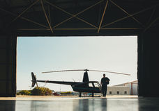 Pilot arriving at the airport with a helicopter in hangar royalty free stock photo