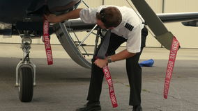 Pilot Attaches Post-Flight Safety Covers and Ribbons Remove Before Flight 2 stock video