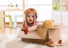 Pilot aviator baby boy with teddy bear toy plays in cardboard box Royalty Free Stock Photo