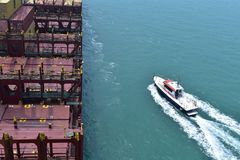 Pilot boat and container vessel. Container vessel arriving to the pilot station and pilot boat approaching Royalty Free Stock Image