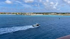 A pilot boat escorting a cruise ship into a caribbean island port stock video
