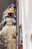 Pilot boat guiding container ship Stock Photo