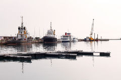 Pilot Boats in a Harbour. A fleet of pilot boats against a harbour wall, on a hazy day Royalty Free Stock Images