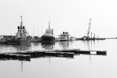 Pilot Boats in a Harbour. A fleet of pilot boats against a harbour wall, on a hazy day, in black and white Royalty Free Stock Images