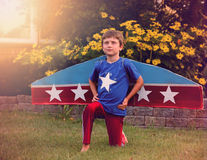 Pilot Boy Pretending to Fly with Wings. A young boy is pretending to be a pilot with wings and stars in his front yard for an imagination or dream concept Stock Images