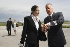 Pilot and a cabin crew checking the time with business travellers in the background Royalty Free Stock Image