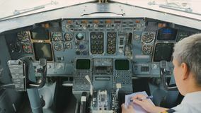 Pilot checks doments sitting in cockpit. Captain of airplane prepares to flight and checks some documents. The man is sitting in cockpit and waits the flight stock footage