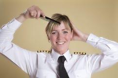 Pilot combing her hair Stock Photography