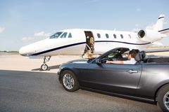 Pilot In Convertible Parked Against Private Jet. At airport terminal Stock Image