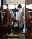 Pilot And Copilot Operating Private Jet. Rear view of pilot and copilot operating private jet Royalty Free Stock Images