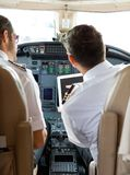Pilot And Copilot Using Digital Tablet In Cockpit Royalty Free Stock Images