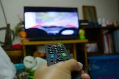 Pilot do TV w ręce i telewizyjnym monitorze Obrazy Royalty Free
