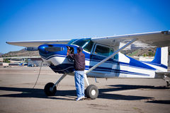 Pilot doing preflight of light aircraft. A private pilot is performing the preflight inspection of an airplane.  Door of engine compartment on Cessna 180 Stock Photos
