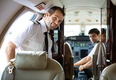 Pilot Entering Private Jet. Portrait of handsome pilot entering private jet with copilot in background stock images