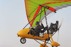 The pilot flies on a yellow motor hang-glider Royalty Free Stock Photography