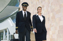 Pilot And Flight Attendant Walking Outside Building Stock Image