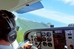 Pilot fly scenic flight above Rarotonga Island in the Cook Islan. Air Rarotonga pilot fly Cessna 172 Skyhawk on a scenic flight above Rarotonga Island the Royalty Free Stock Image