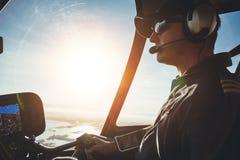 Pilot- flyg en helikopter på en solig dag Arkivfoton