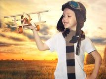 Pilot- flygare f?r barn med flygplandr?mmar av resanden i sommar i natur p? solnedg?ngen fotografering för bildbyråer