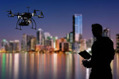 Pilot is flying the drone with the camera with skyline city background Royalty Free Stock Image