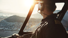 Pilot flying a helicopter and looking outside the window. Close up of a male pilot flying a helicopter and looking outside the window with sun flare entering the Royalty Free Stock Photos