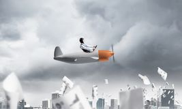 Pilot flying in small paper airplane stock image