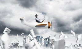 Pilot flying in small paper airplane. Crisis management and control in difficult situation concept. Businessman in aviator hat driving propeller plane in storm royalty free stock photo