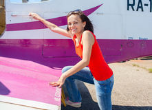 Pilot girl entering cabin of little plane Royalty Free Stock Photography