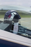 Pilot helmet in plane cockpit. A pilot helmet in the cockpit of a plane with flight plan or diagram on dashboard Stock Photography