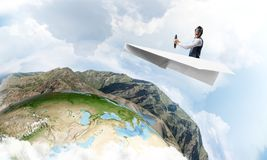 Pilot im ledernen Sturzhelm, der Papierflugzeug f?hrt stockfoto