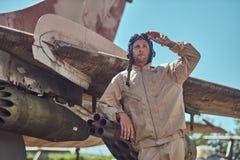 Pilot im Uniform- und Fliegensturzhelm, der nahe einem alten Kriegsabfangjäger in einem Freiluftmuseum steht Lizenzfreie Stockbilder