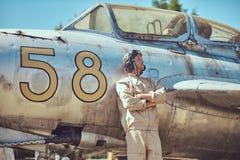 Pilot im Uniform- und Fliegensturzhelm, der nahe einem alten Kriegsabfangjäger in einem Freiluftmuseum steht lizenzfreie stockfotos