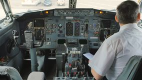 Pilot inside the cockpit. Captain of airplane prepares to flight and checks some documents. The man is sitting in cockpit and waits the flight. Interior of stock video