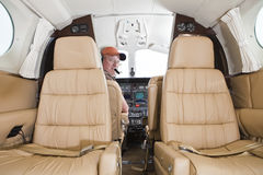 Pilot looking at passenger compartment Stock Images