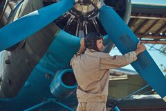 Pilot or mechanic in a full flight gear checks the propeller of his retro military aircraft before a flight. Royalty Free Stock Images