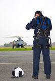 Pilot near helicopter. Rear view of male helicopter pilot stood on airfield with helmet on floor, rescue helicopter in background royalty free stock photo