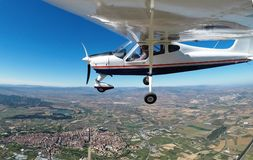 PILOT OVERFLYING A TOWN WITH A AIRCRAFT SINGLE ENGINED AND HIGH WING AIRCRAFT stock image