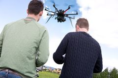 Pilot and Photographer with Photography Drone. Pilot and photographer using an octocopter UAV to shoot aerial photographs royalty free stock photo