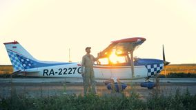 Pilot- rörande vingar en på ett ljust flygplan som chekcing dem, tätt upp stock video
