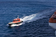 A pilot rescue boat and lifeboats. A pilot rescue boat approaches a ship with her lifeboats stowed Stock Photos
