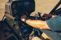 Pilot's hand on an helicopter instrument panel. Royalty Free Stock Image