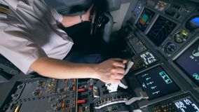 Pilot`s hand holding for a control lever during flight. Modern passenger airplane cabin interior.
